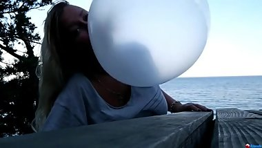 Blondie outside blowing huge gum bubbles